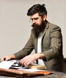 在打字机的有胡子的人类型 有长的胡子的人和髭打字研究论文 在衣服工作的商人  图库摄影