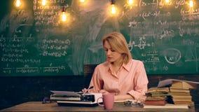 在打字机的老师键入的文本在学校课程的一张桌上坐一个绿色委员会背景的 影视素材