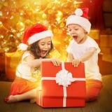 在打开礼物盒的圣诞老人帽子的愉快的孩子 免版税库存照片