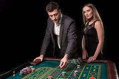 在打赌在轮盘赌的赌博娱乐场的典雅的夫妇,在黑背景 免版税库存图片