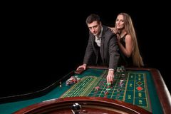 在打赌在轮盘赌的赌博娱乐场的典雅的夫妇,在黑背景 图库摄影