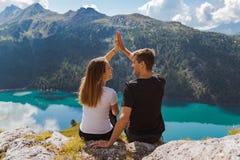 在打高五在与美好的全景的一个岩石的爱的年轻夫妇作为背景 瑞士阿尔卑斯 免版税库存照片
