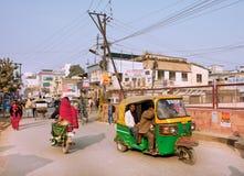 在打鸣的街道上的自动人力车 免版税库存照片