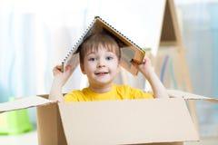 在托儿所哄骗使用在一个玩具房子里的男孩 免版税库存图片