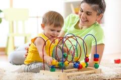 在托儿所在家哄骗与教育玩具的男孩戏剧 看她聪明的儿子的愉快的母亲 免版税图库摄影