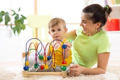 在托儿所在家哄骗与教育玩具的男孩戏剧 看她聪明的儿子的愉快的母亲 库存照片