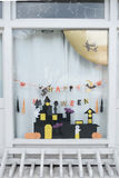 在托儿所房子的窗口的逗人喜爱的孩子纸工艺显示庆祝的天10月31日,万圣夜 免版税库存图片
