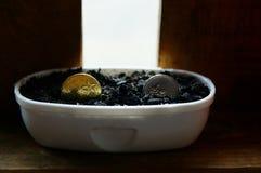 在托儿所罐的金和银币 库存照片