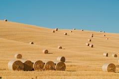 在托斯卡纳的亩茬地的圆的干草捆 免版税库存照片