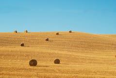 在托斯卡纳的亩茬地的圆的干草捆 免版税库存图片
