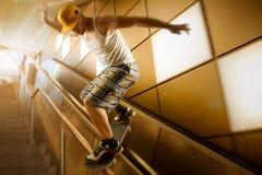 滑在扶手栏杆下的年轻溜冰板者 库存图片