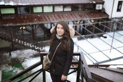 在扶手栏杆后在一个距离站立并且看在冬天的一件黑短的皮大衣的女孩` s画象 免版税库存图片