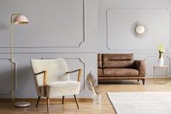 在扶手椅子旁边的桃红色灯在与金叶和明亮的地毯的灰色公寓内部 库存照片