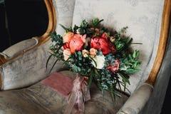 在扶手椅子的新娘花束 免版税库存照片