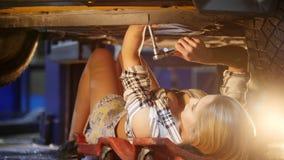 在技工服务工作里面的自动汽车 有说谎在汽车下和固定它的图的年轻女人 与板钳一起使用 影视素材
