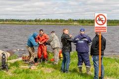 在技术水库的岸的警报信号与题字游泳的被禁止 在背景中,潜水的工作 免版税库存照片