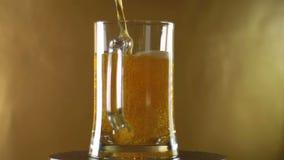 在把变成在金黄背景之上的一种被倾倒的黑啤酒的一个大杯子,慕尼黑啤酒节 股票录像