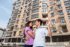 在把握门关键和看彼此的新的家前面的夫妇 免版税库存照片