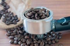 在把柄的咖啡豆在桌上 库存照片