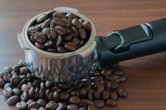 在把柄的咖啡豆在桌上 库存图片
