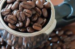 在把柄的咖啡豆在桌上 免版税库存图片