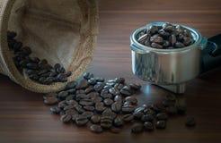 在把柄的咖啡豆在桌上 图库摄影