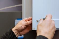 在把柄设施门的手在有螺丝刀的厨柜 库存图片