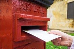 在投入信件的一只男性手上的特写镜头在一红色letterbox 通信的葡萄酒类型的概念 免版税库存照片