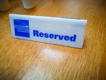 在投入在木桌的后备的标志的美国运通商标在咖啡馆餐馆 图库摄影