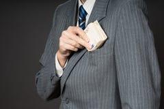 在投入钞票的衣服的商人在他的夹克衣胸袋 商人拿着现金,堆五十欧元金钱 Pers 免版税库存照片