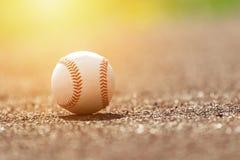 在投手土墩的棒球球 在日落的棒球场 免版税库存照片