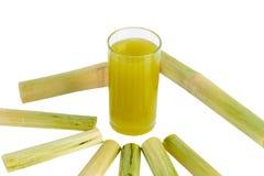 在投手的新鲜的被紧压的糖蔗汁有被切开的片断藤茎的 库存照片
