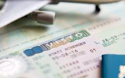 在护照的申根签证到意大利和飞机的一次旅行的 库存照片
