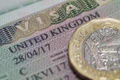 在护照的英国签证与一1英镑硬币 库存图片