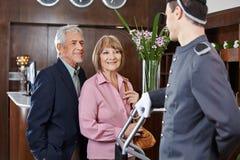 在报到的资深夫妇在旅馆 库存图片