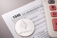 在报税表的Ethereum物理硬币标志与计算器 库存图片