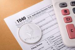 在报税表的Ethereum物理硬币标志与计算器 库存照片