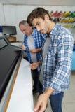 在报纸工厂供以人员推挤巨大的卷轴式记录纸 免版税库存照片