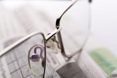 在报纸特写镜头视图的玻璃 免版税库存图片