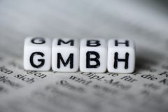在报纸的木字母表块形成的德国词GMBH 库存照片