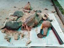 在报纸的破碎石块和工具 图库摄影
