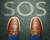 在报警信息SOS前的人在沥青 图库摄影