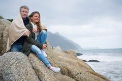 在披肩包裹的夫妇坐岩石 免版税库存图片