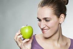 在抵抗在新鲜水果和饮食的标志的快乐的华美的20s女孩的特写镜头 库存照片