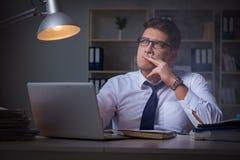 在抽烟在办公室的重音下的商人 免版税库存图片