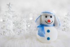 在抽象冬天冰树背景的滑稽的原始的雪人 免版税库存图片