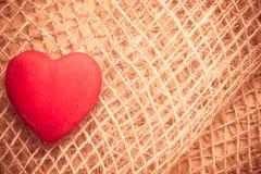 在抽象布料背景的红色心脏 库存图片