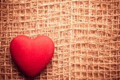 在抽象布料背景的红色心脏 免版税库存图片