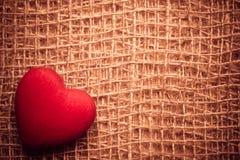 在抽象布料背景的红色心脏 免版税库存照片