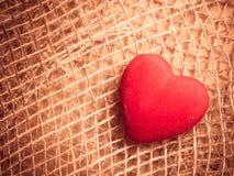 在抽象布料背景的红色心脏 图库摄影